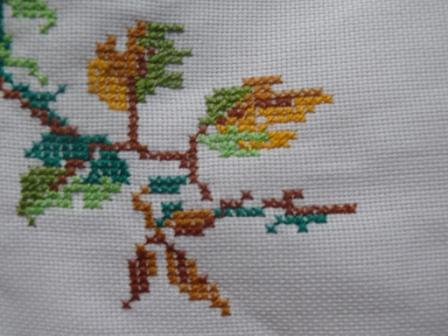 6. sulaman kristik taplak meja motif daun warna hijau dan batang warna coklat muda.