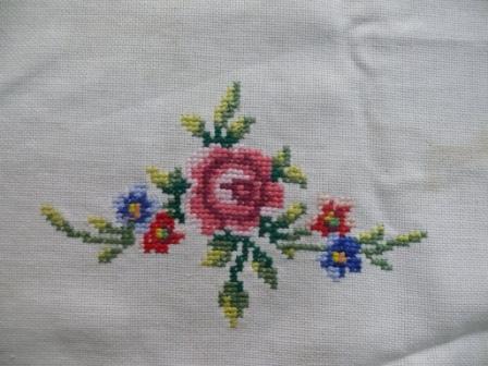 4. sulaman kristik taplak meja motif bunga rose ukuran kecil di kelilingi daun.